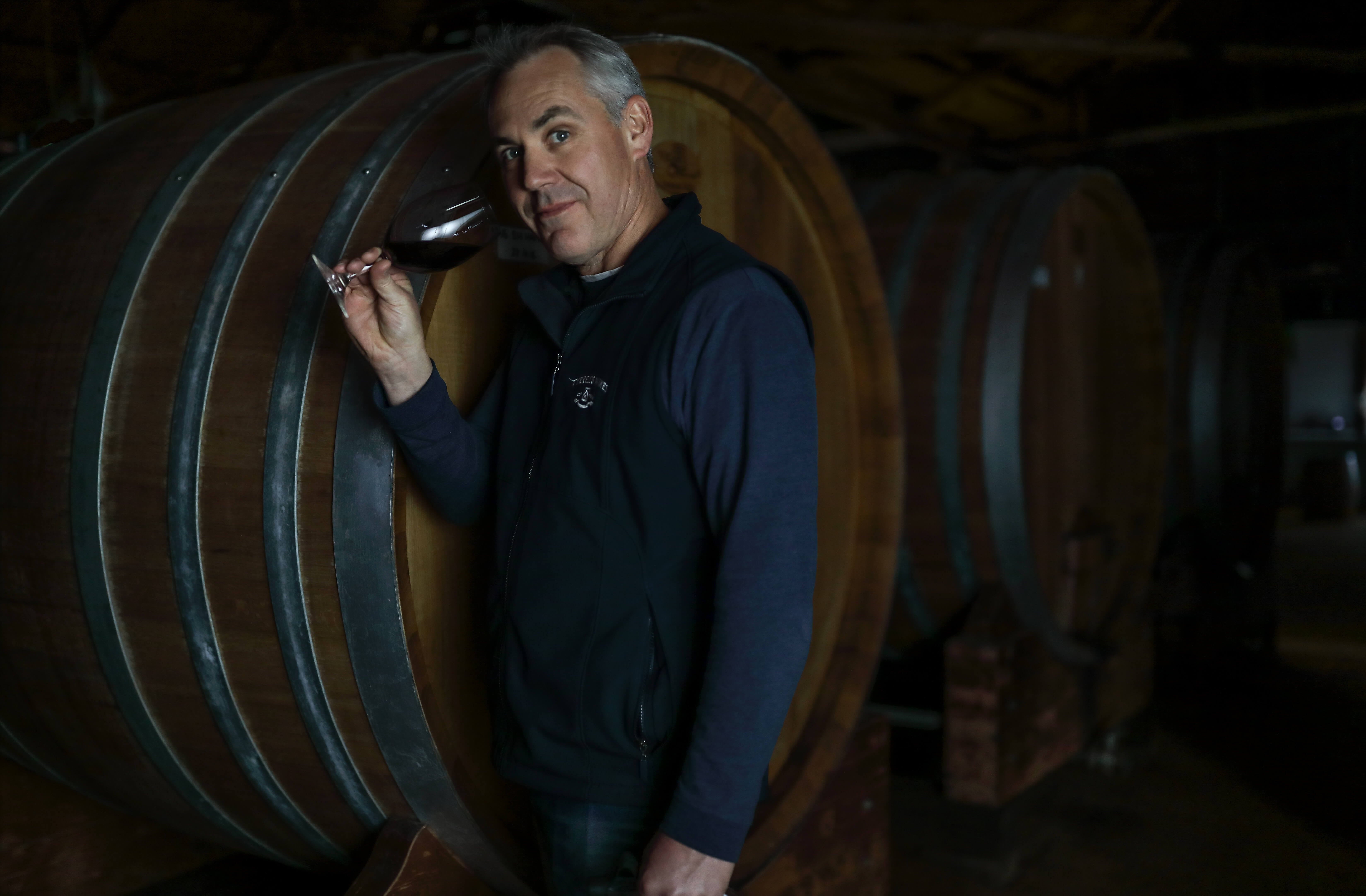 Portrait of winemaker in low light.
