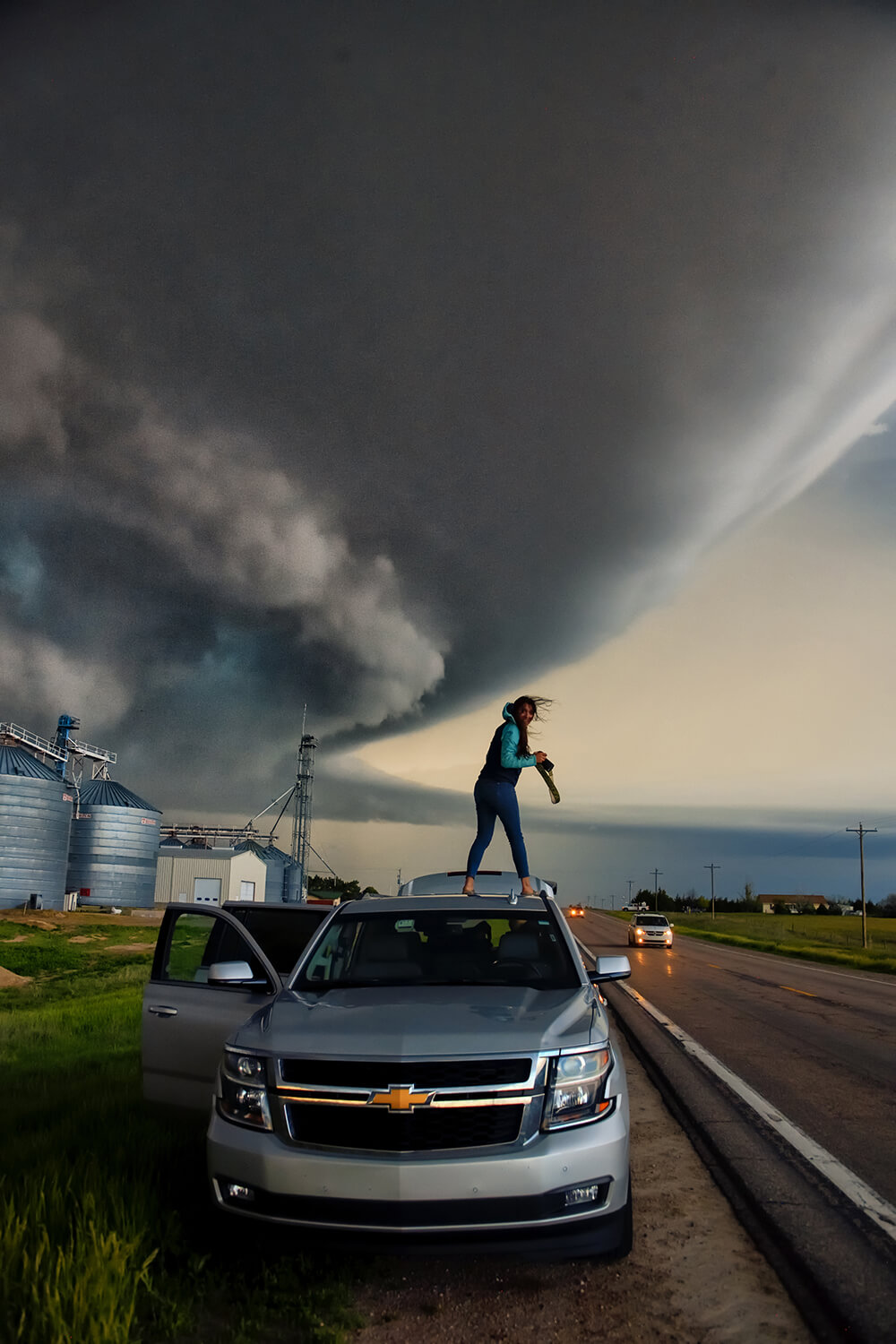 Photographer on top of a car shooting the tornado