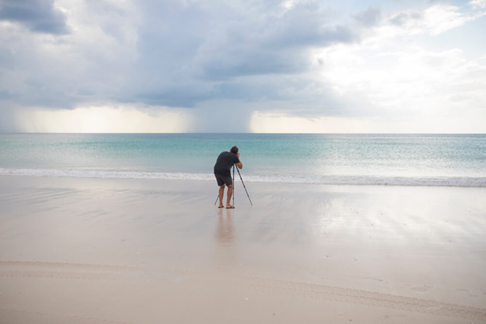 Photographer using a tripod to take a seascape image