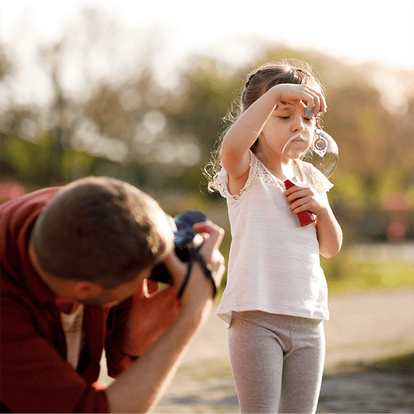 Father capturing image of child blowing bubbles