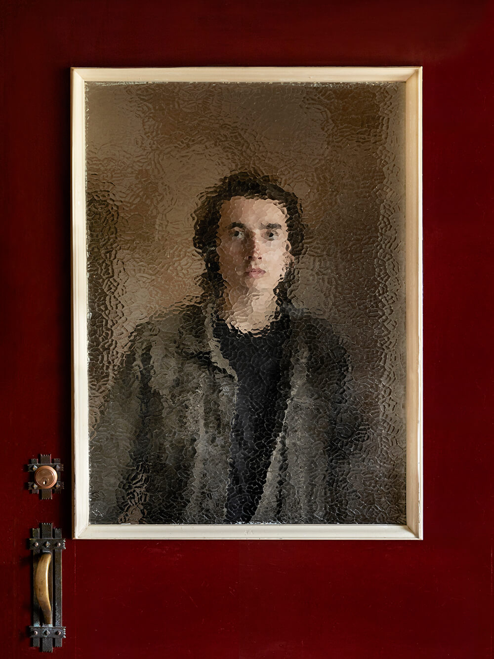 Portrait image of person behind door