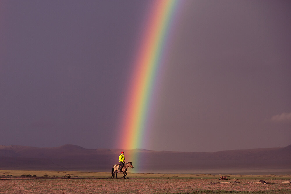 Landscape image of man on horse at rainbow