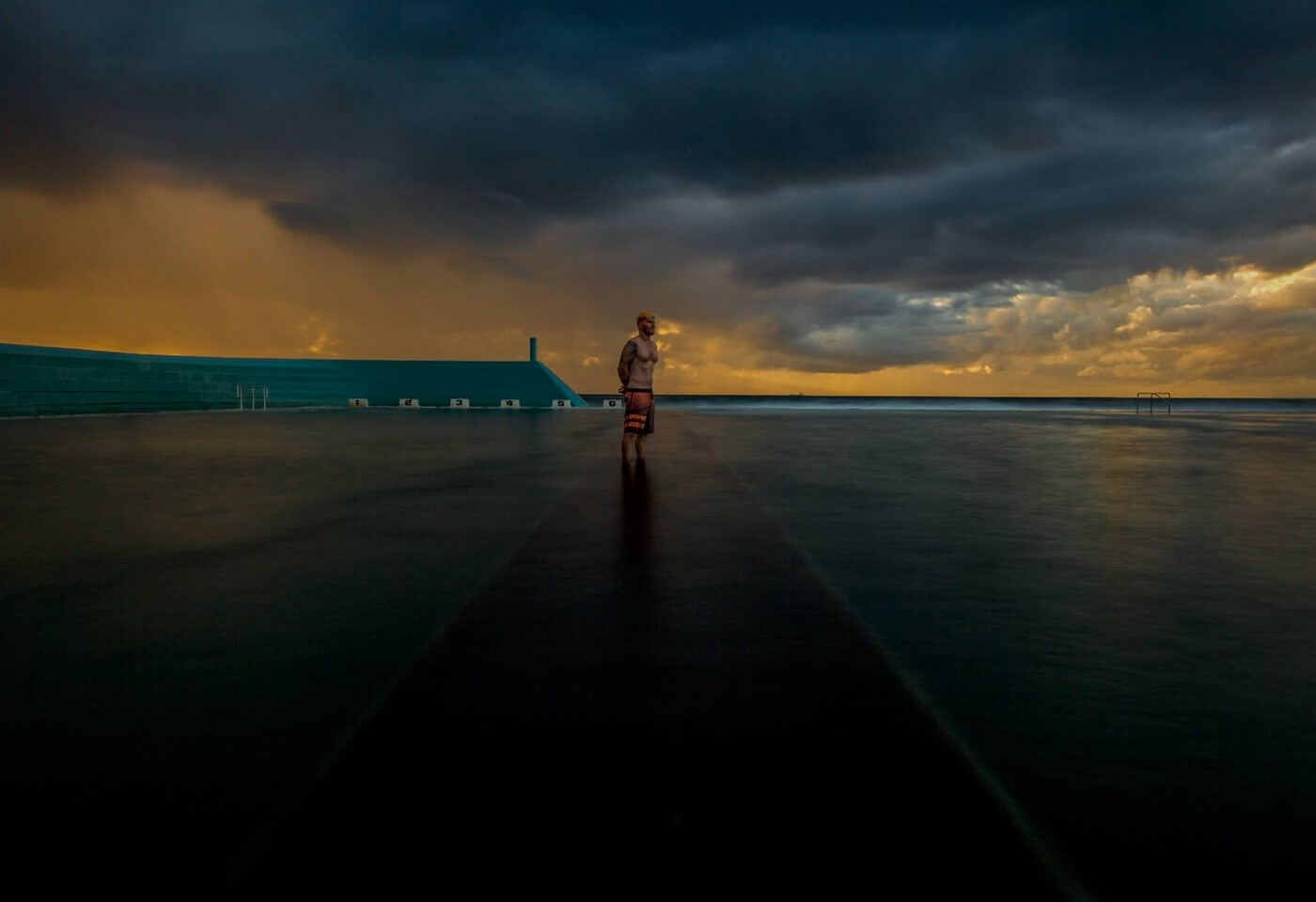 Image of man standing in beach pool at dawn