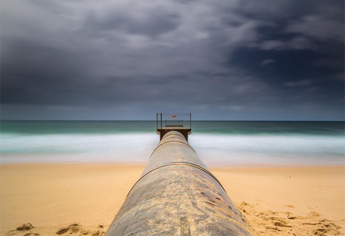 Long exposure image of a pipe leading out to the beach