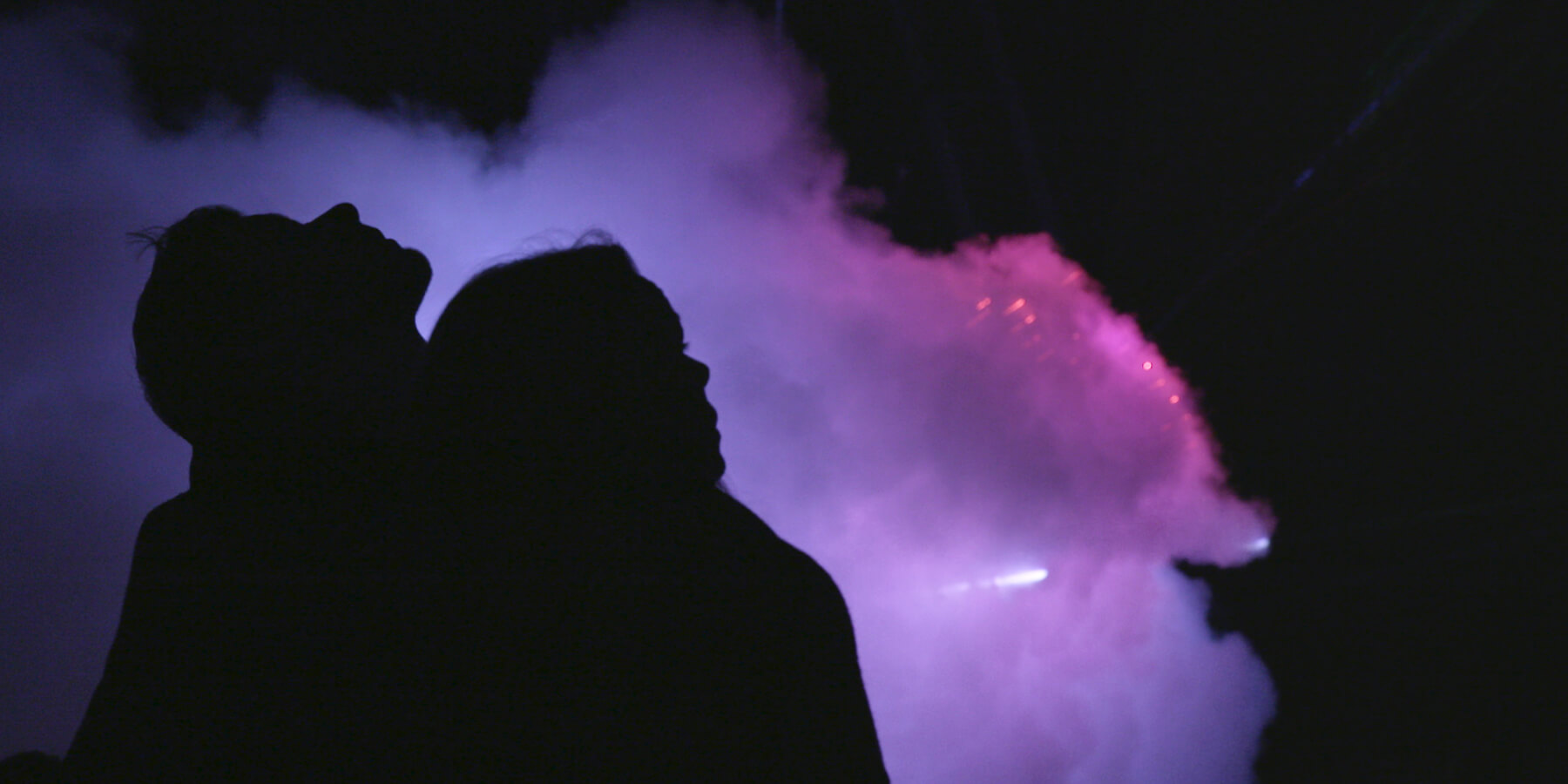 Image of silhouette in front of coloured smoke