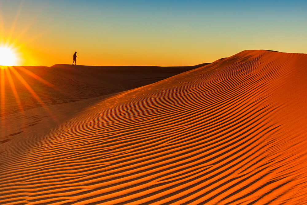 Man on top of a sand dune
