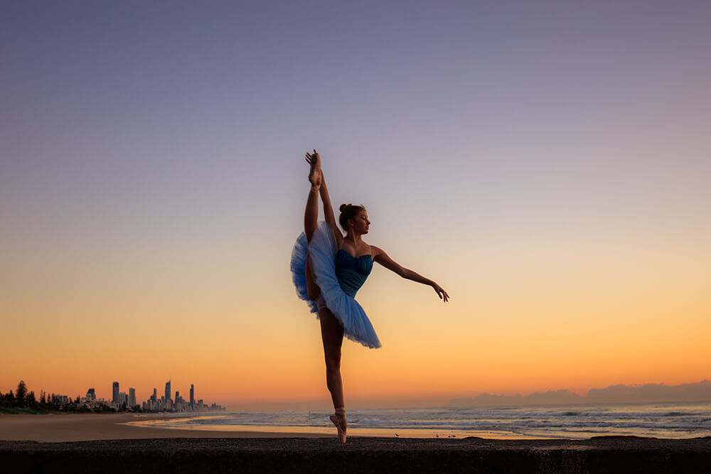 Ballerina dancing on the beach at sunset
