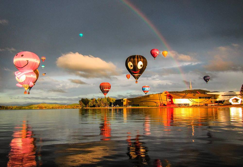 Hot air balloon at sunrise with rainbow