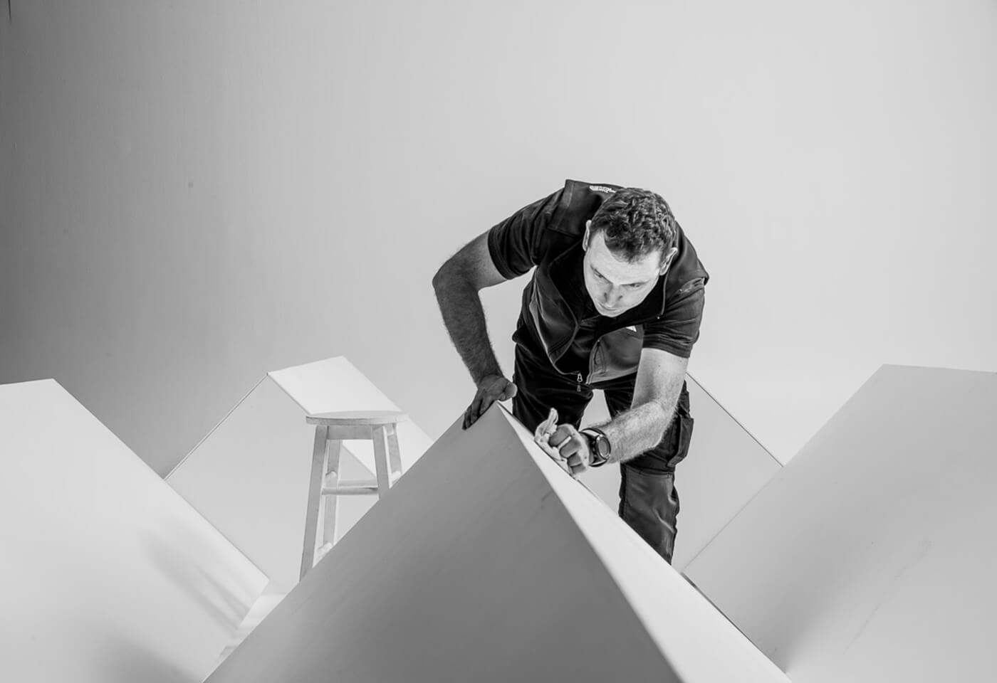 Black and white photo of photography assistant preparing props in studio