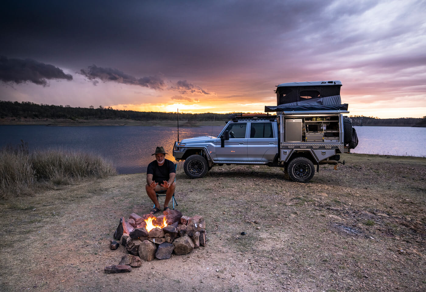 Image of man with a hat warming hands by fire in front of a 4WD.