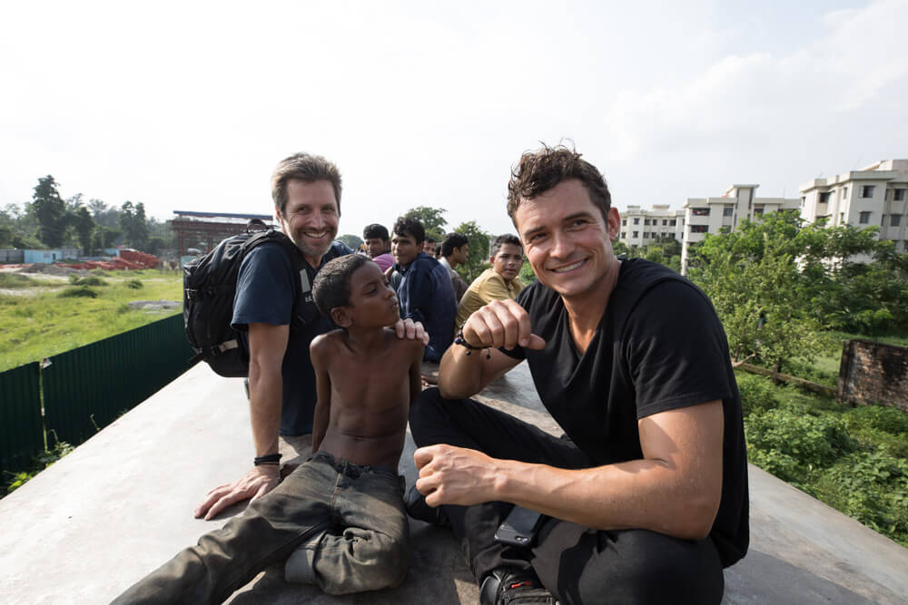 photo of Simon Lister and Orlando Bloom with children on top of a train in Bangladesh