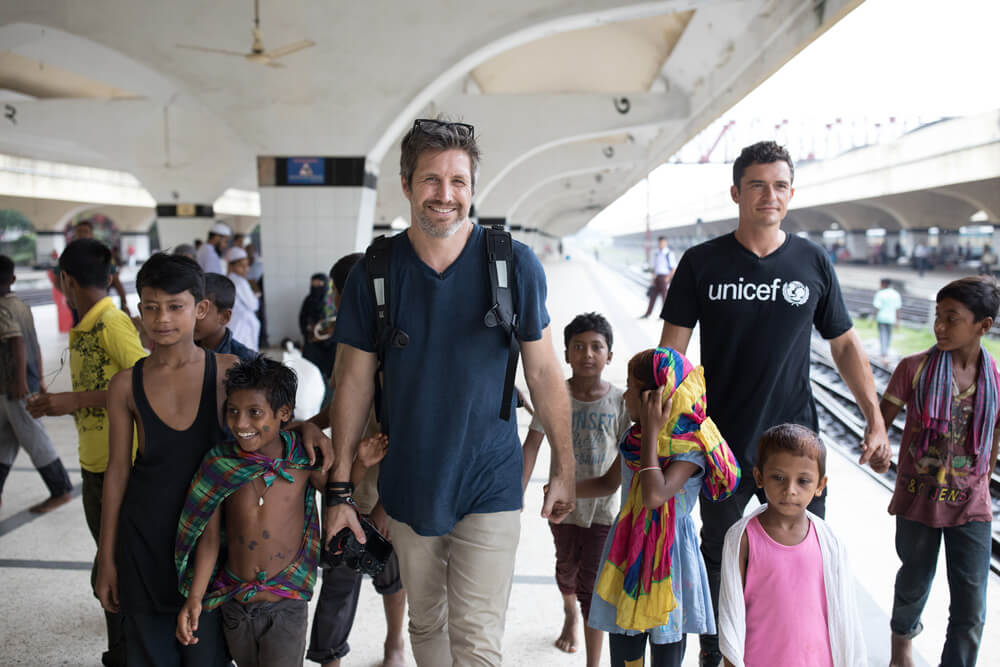 Orlando Bloom and Simon Lister with children in Bangladesh
