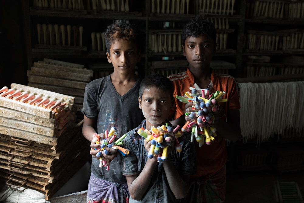 portrait photo of working children at a balloon factory in Bangladesh