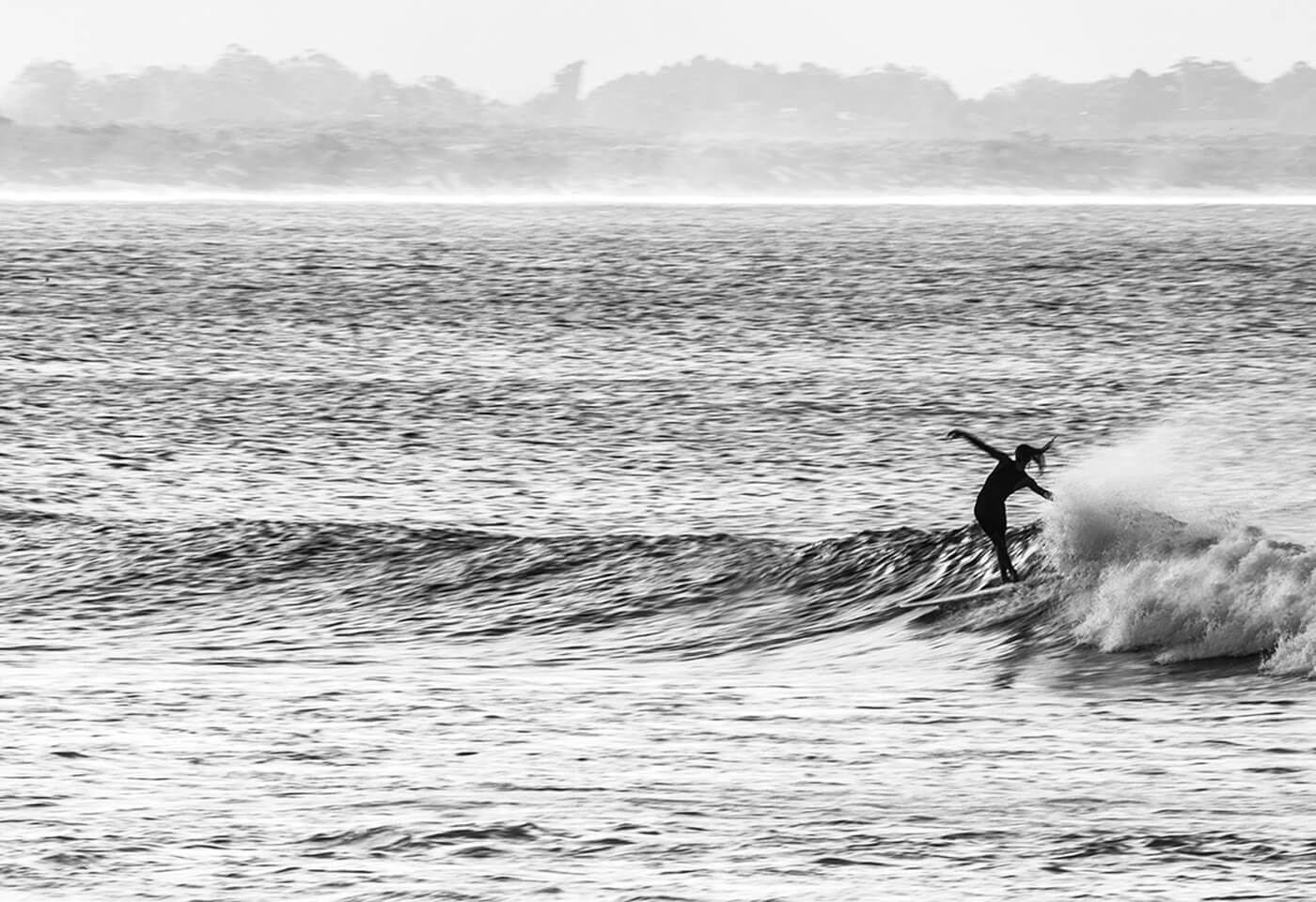black and white image of a female surfer riding a wave