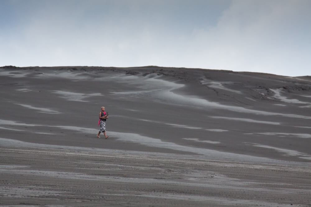Person walking on dark sand
