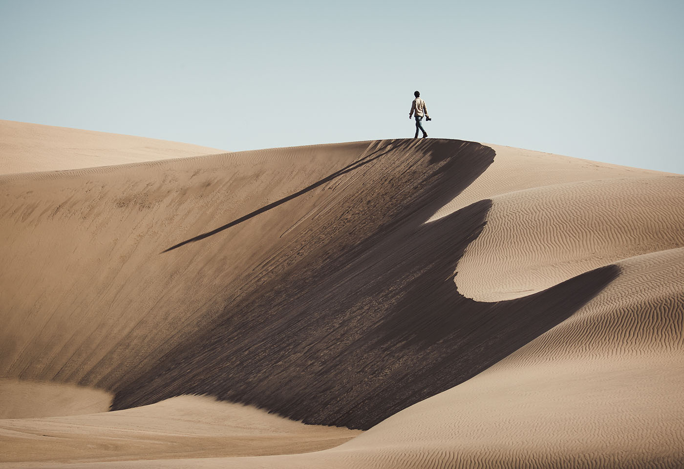 Landscape image of man on sand dunes